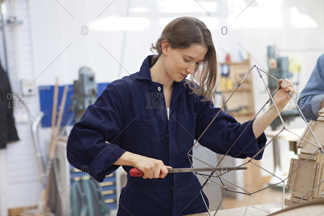 Young woman in coveralls filing wire frame