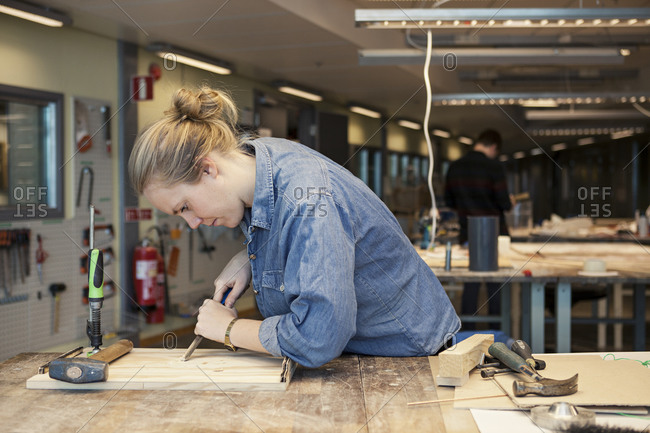 Young woman chiseling a wood plank