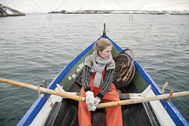 Norwegian fisherwoman rowing a boat in harbor