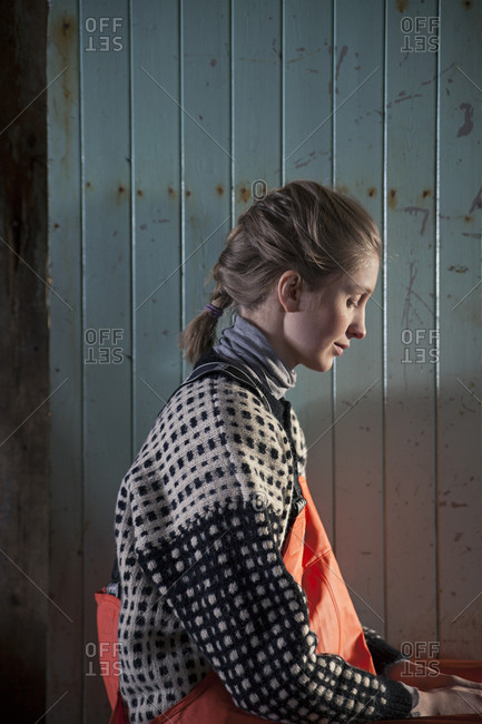 Norwegian woman in wool sweater and waterproof coveralls in fishing shed