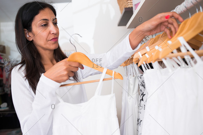 Business owner hanging white blouse on clothes rack