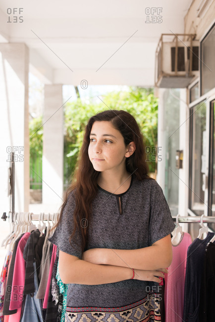 Teenager Standing Outside A Clothing Boutique With Her Arms