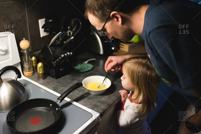 Toddler girl watches her father beat eggs in a bowl