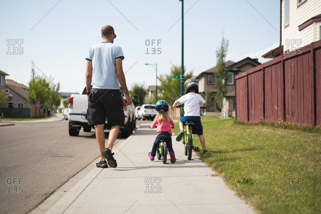 Man watches his young children ride bicycles on sidewalk