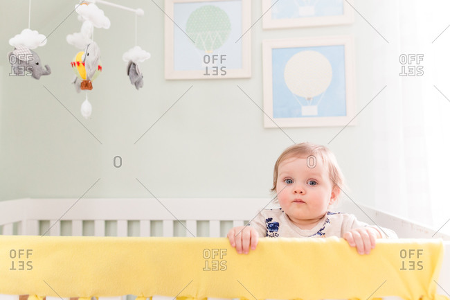 Toddler standing along the edge of her crib waving