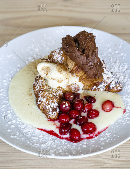 Pastry with pudding and cranberries dusted with powdered sugar