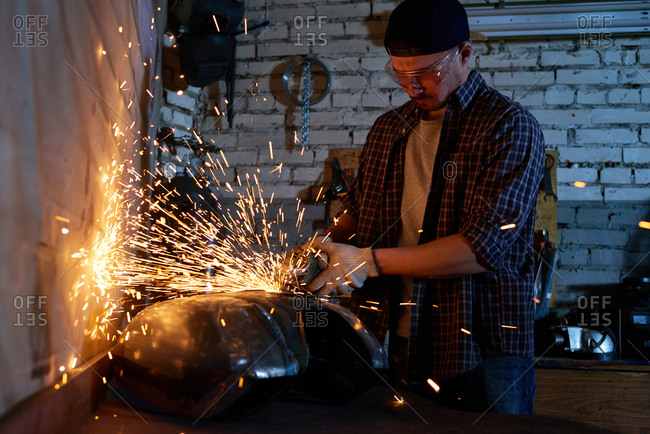 Sparks fly as a mechanic uses a power tool on motorcycle part