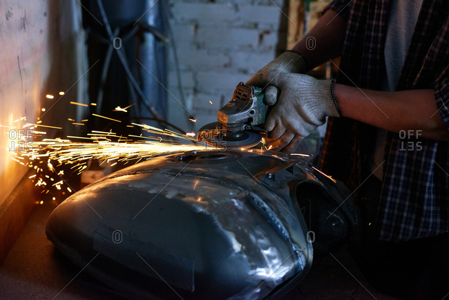 Close up of mechanic using a metal grinding tool on motorcycle tank