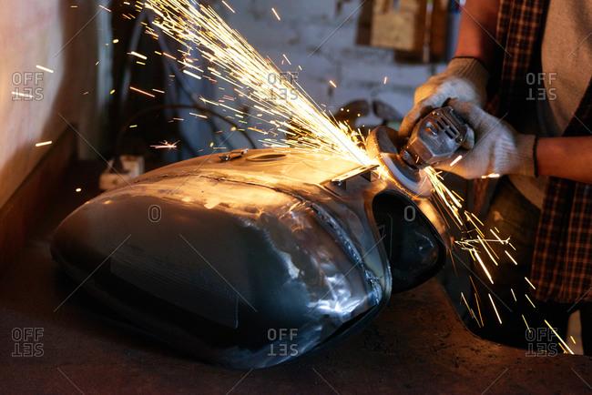 Metal grinding tool emits sparks as mechanic works on motorcycle tank
