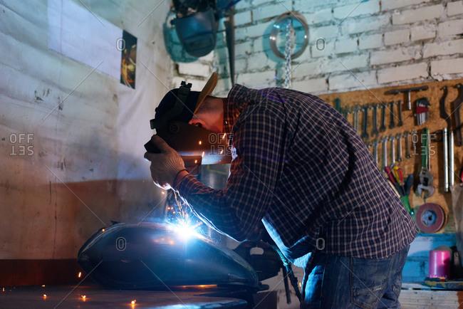 Welder working on motorcycle tank