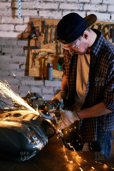 Mechanic in safety glasses uses power tool on motorcycle tank