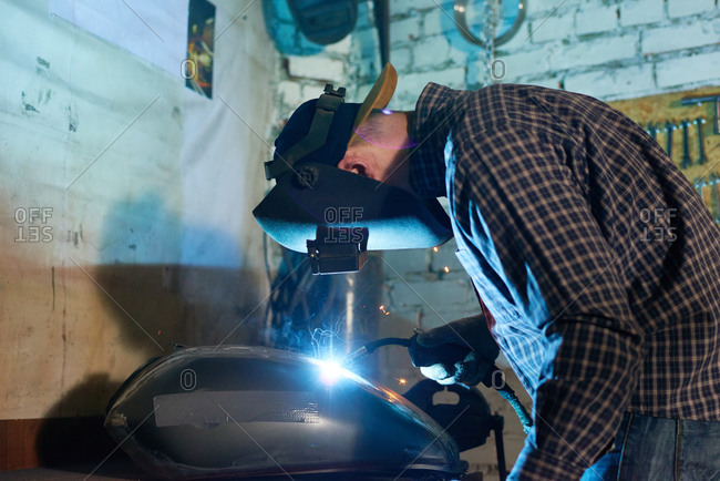 Welder in a face mask uses a torch to repair a motorcycle tank