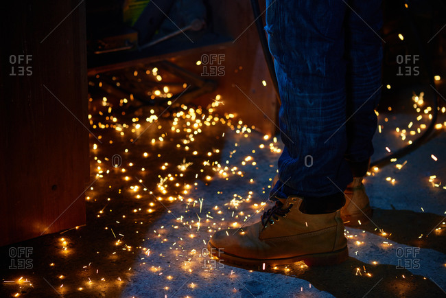 Sparks on the floor surround welder's boots in workshop