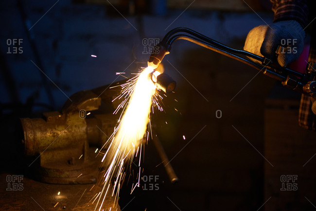 Man using welding torch on piece of metal in a vice