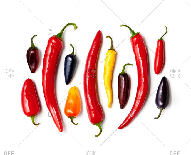 Various colored hot peppers in a line