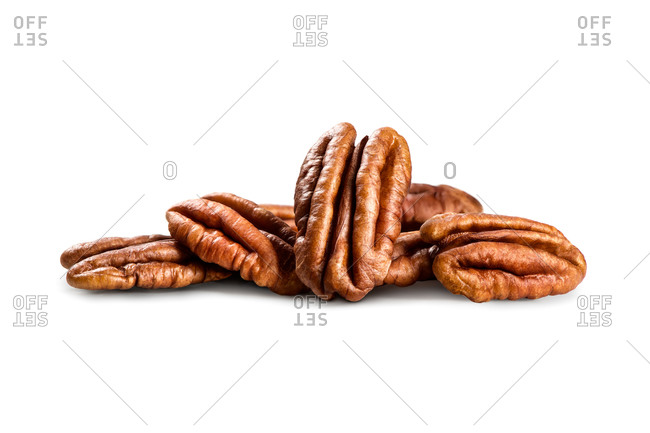 Pile of shelled pecans on a white background