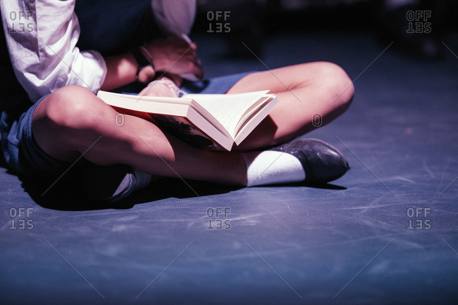 Crossed legs of girl with book