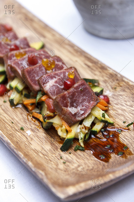 Slices of rare meat served over vegetables on wooden tray