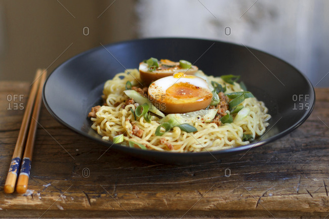 Plate of ramen noodles with hard boiled eggs and scallions
