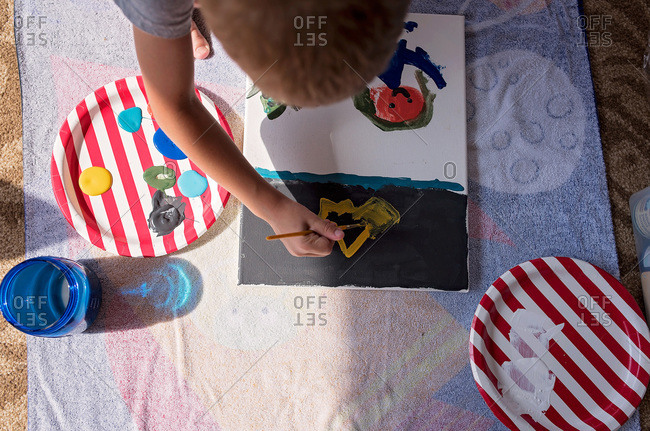 Overhead view of a child sitting on the floor painting