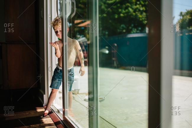 Boy standing in the open doorway of a sliding glass door
