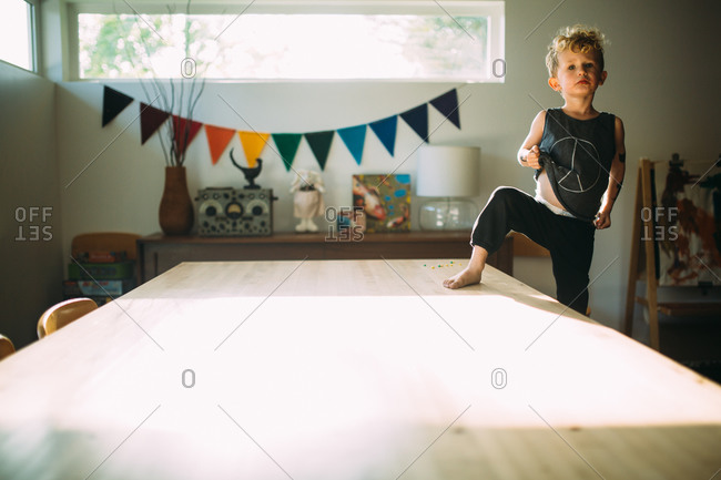 Boy standing with one foot on the table as he lifts up his shirt