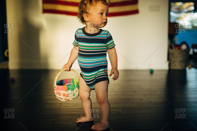 Toddler boy wearing a onesie and holding a basket