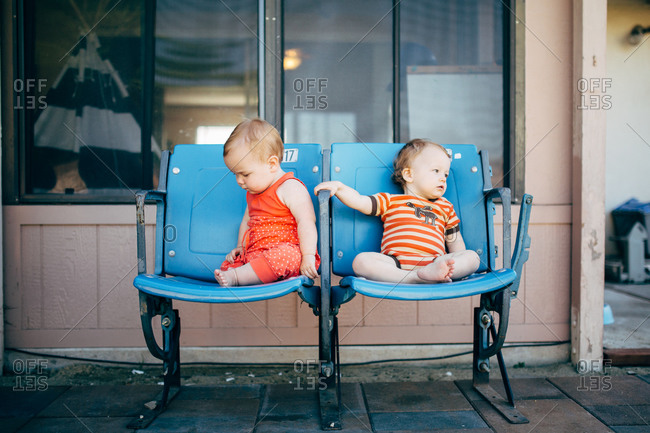 Two babies sitting on old chairs on the sidewalk