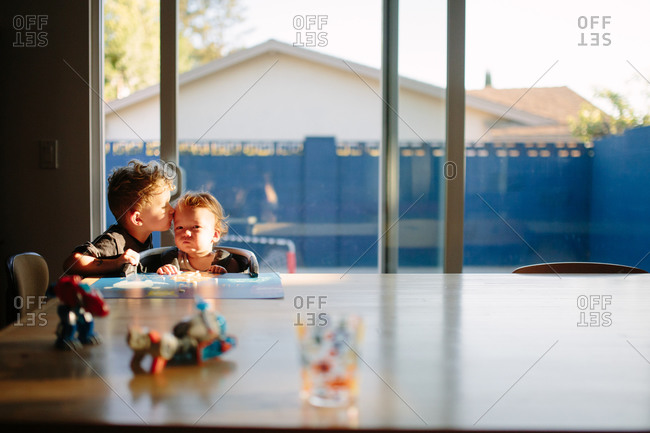 Young boy kisses his toddler brother at dining table
