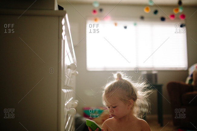 Young toddler girl playing with toy in bedroom