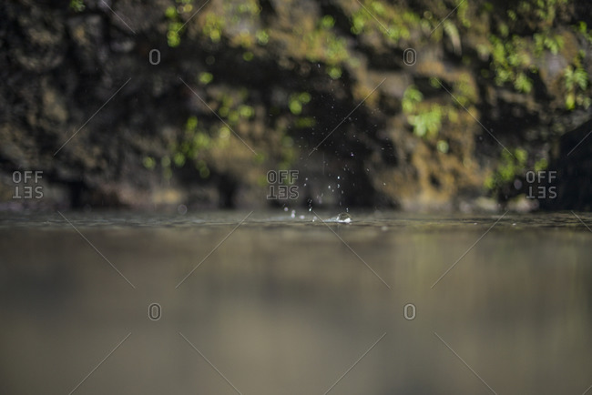 Close up of rain drops landing in water in a cave
