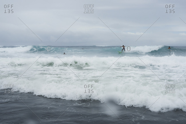 Surfers in the Pacific ocean riding waves near Mo'orea Island, French Polynesia