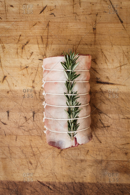 Raw meat with rosemary tied with twine