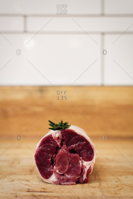 Raw meat with a sprig of rosemary on a wooden counter