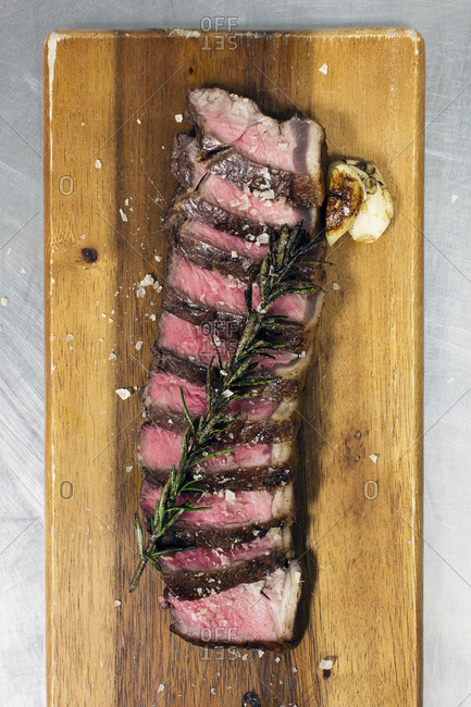 Sliced beef roast on a cutting board with rosemary