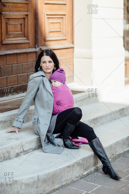 Babywearing mother sitting on steps with her child