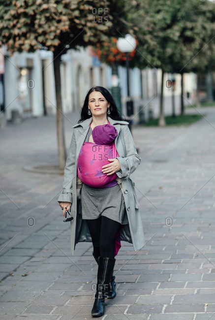 Portrait of trendy babywearing mother walking in the city