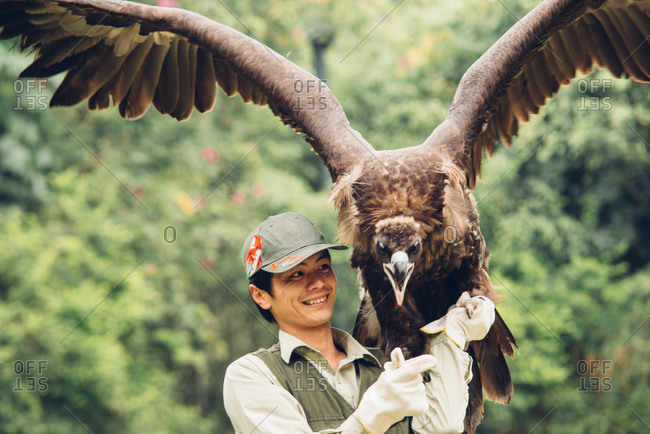 Chinese man with falcon in hand in Guangzhou, China