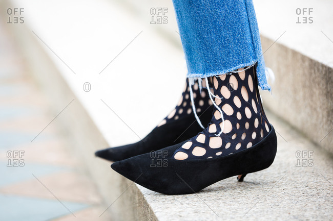 Close up of woman in black pumps with cutouts