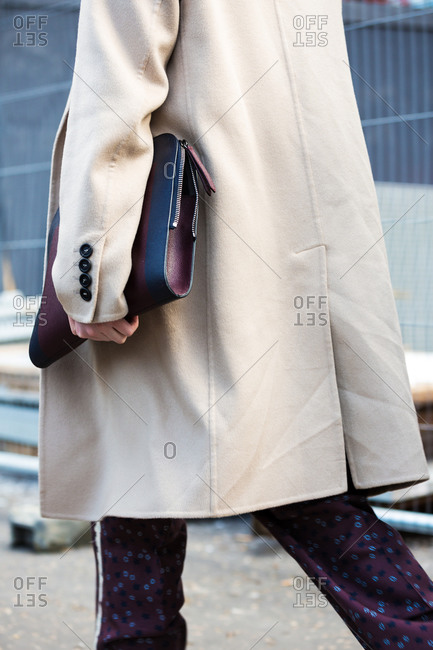 Woman walking in a beige coat and burgundy pattern pants