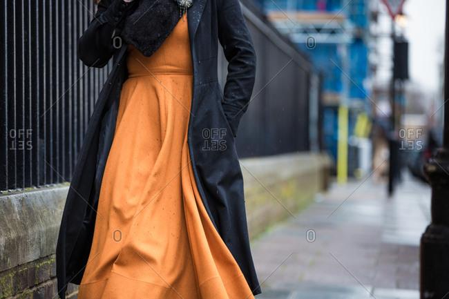 Woman in an orange dress walking in the rain