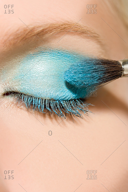 Close of woman applying blue eye shadow
