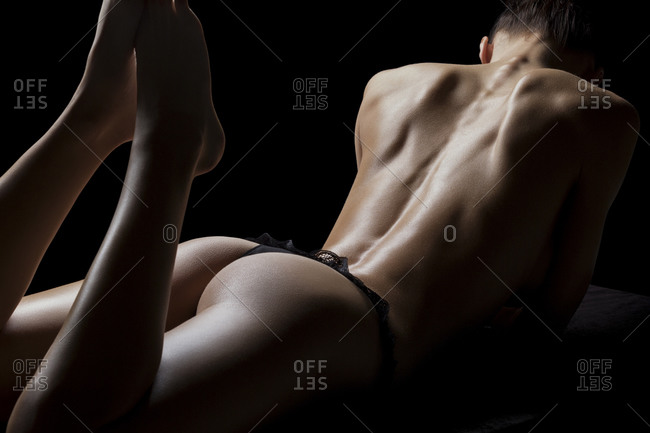 Woman lying on her stomach posing in a black thing