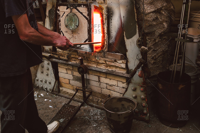 Man putting blowpipe in oven