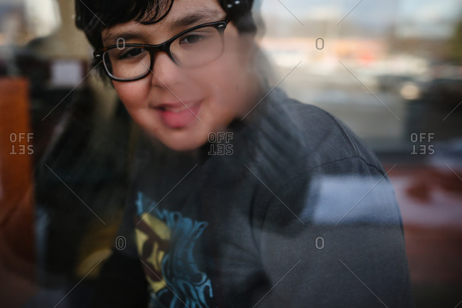 Boy looking out a window with condensation on it