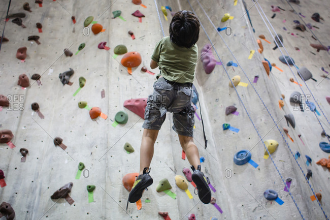 Boy dangling on a rope while trying to climb an indoor rock wall