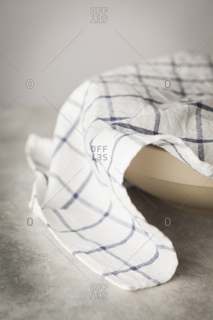 Kitchen towel covering a bowl to keep bread dough warm while letting it rise