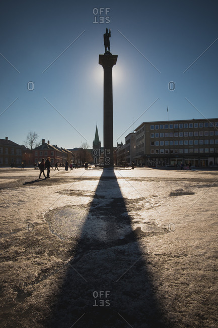 Monument casting shadow on an icy city square