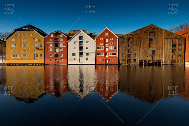 Colorful buildings standing side-by-side reflected in a still blue river