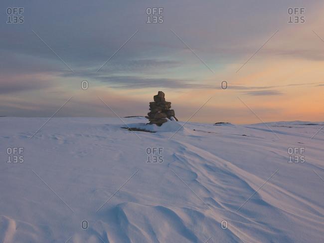 Marker stone and snowdrifts along a barren hillside